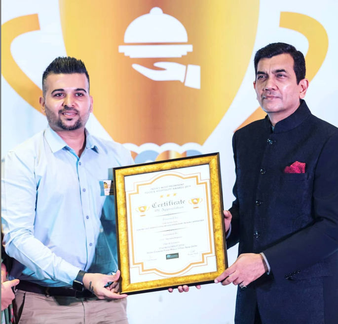 """Vikas Solanki receiving """"India's Most Prominent Food and Hospitality Award, 2019"""" from Chef Sanjeev Kapoor"""