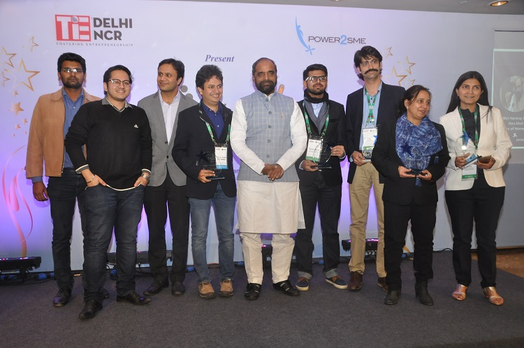 Shri Hansraj Ahir, MoS Home Affairs, Govt of India in the center, (from right) Ms. Sonal, Founder & Director, Compassionate Choices, Dr. Vibha Tripathi, CEO, Swajal Water, Ankit Mehta, CEO, ideaForge Technology, Mr. Parth Dave, Co-founder & COO, Frolitic Energy Solutions, Hona'ble MoS, and Mr. Mr. Prasoon Gupta, CEO, Sattviko Lifestyle with his team