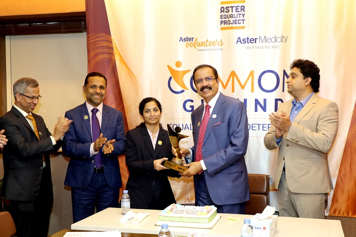 Dr. Azad Moopen awarding a person of determination working with Aster DM Healthcare