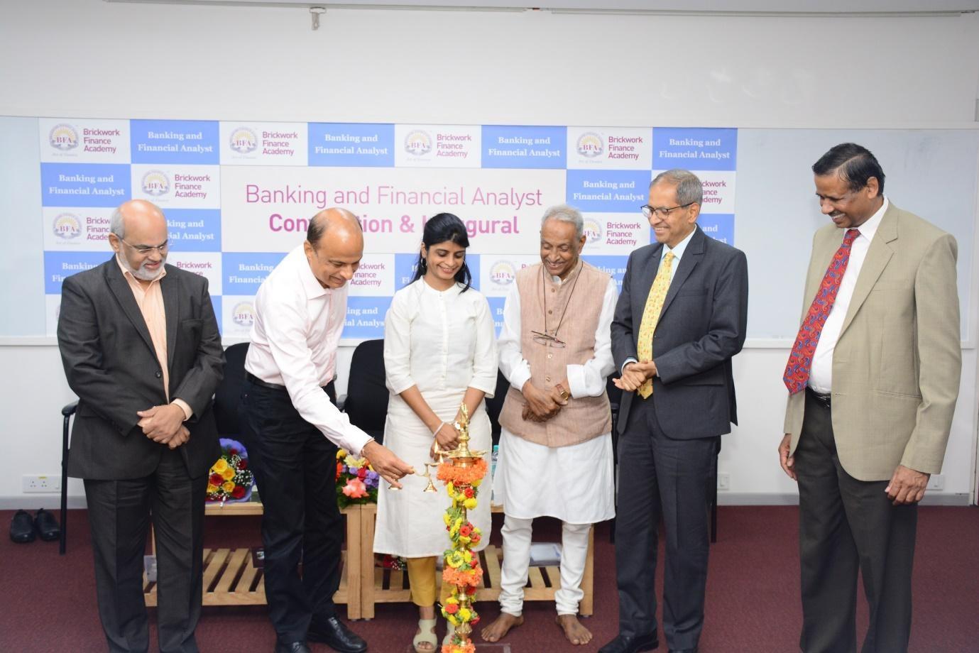 (L-R) Shri Santosh Kamath is seen lighting the lamp along with Shri D Ravishankar, Ms. Hema Sethia (topper of the Class of 2018), Prof. KRS Murthy, Shri Vivek Kulkarni and Shri MSR Manjunatha, Head Ratings Administration, Brickwork Ratings